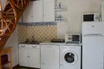 La partie cuisine avec lave-linge, lave-vaisselle, réfrigérateur-congélateur, four grill, four micro-ondes, table de cuisson deux feux vitrocéramiques avec vue sur mer par une large fenêtre double